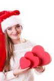 O chapéu do ajudante de Santa da menina guarda caixas de presente dadas forma coração Fotografia de Stock Royalty Free
