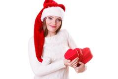 O chapéu do ajudante de Santa da menina guarda caixas de presente dadas forma coração Imagem de Stock