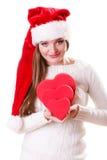 O chapéu do ajudante de Santa da menina guarda caixas de presente dadas forma coração Imagem de Stock Royalty Free
