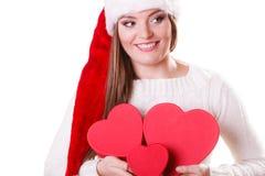 O chapéu do ajudante de Santa da menina guarda caixas de presente dadas forma coração Imagens de Stock
