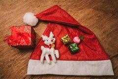 O chapéu e a caixa de presente vermelhos com uma rena branca brincam Imagens de Stock Royalty Free