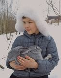 O chapéu exterior do sorriso do bebê da estação do parque natural da cara do coelho bonito fora caçoa pouco menino branco do frio Imagem de Stock