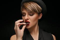 O chapéu negro vestindo da mulher atrativa e o t-shirt clássico comem o chocolate em um fundo escuro imagem de stock royalty free
