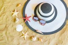 O chapéu, os óculos de sol, as estrelas do mar e as conchas do mar na areia encalham Fotografia de Stock Royalty Free