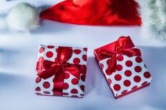 O chapéu vermelho de Santa envolveu a caixa atual na superfície branca imagem de stock royalty free