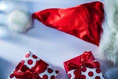 O chapéu vermelho de Santa envolveu a caixa atual no fundo branco imagens de stock royalty free