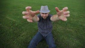 O chapéu vestindo do homem novo da forma está sentando-se na grama e no levantamento video estoque