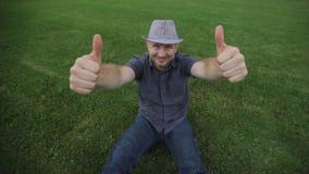O chapéu vestindo do homem novo da forma está sentando-se na grama e no levantamento filme