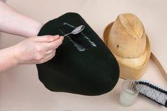 O chapeleiro aplica um esparadrapo uma capa de feltro para dar forma Fotografia de Stock