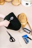 O chapeleiro aplica um esparadrapo uma capa de feltro para fixar Imagem de Stock