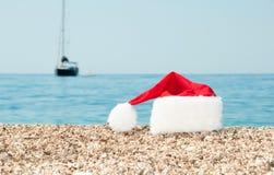 O chapéu do Natal encontra-se na praia. Imagens de Stock