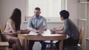 O chefe bonito da mulher que escuta o homem japonês novo na entrevista de trabalho no escritório moderno, empregado caucasiano ju video estoque