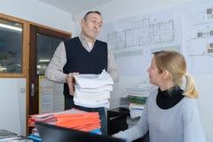 O chefe dá afastado o trabalho para o assistente Fotografia de Stock