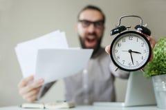 O chefe irritado com barba guarda o despertador e os papéis que grita sobre Fotografia de Stock Royalty Free