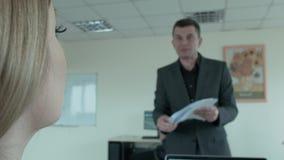 O chefe no fundo, borrado com papéis em sua mão, aproxima a menina, grita no seu e joga os papéis vídeos de arquivo