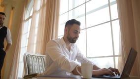 O chefe verifica o interno que trabalha no portátil sobre o fundo da janela vídeos de arquivo