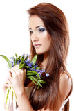 O cheiro adolescente bonito da menina e aprecia a fragrância da flor do snowdrop Imagens de Stock