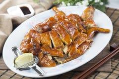 O chinês desbastou a galinha grelhada na placa branca na tabela em r imagens de stock royalty free
