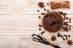 O chocolate, baunilha cola, a canela, feijões de café no fundo de madeira branco com espaço da cópia para seu texto Vista superio imagens de stock