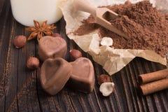 O chocolate coração-deu forma a doces em um fundo rústico, composição do chocolate fotografia de stock