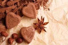 O chocolate coração-deu forma a doces em um fundo rústico, composição do chocolate foto de stock