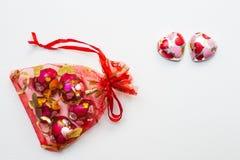 O chocolate coração-deu forma no saco vermelho no fundo branco fotografia de stock royalty free