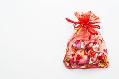 O chocolate coração-deu forma no saco vermelho no fundo branco imagem de stock royalty free