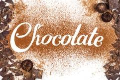 O chocolate da palavra escrito pelo pó de cacau com chocolate escuro a Fotografia de Stock