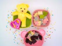 O chocolate e a boneca decoram o romance do tema e agradáveis Imagens de Stock