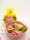 O chocolate e a boneca decoram o romance do tema e agradáveis Fotografia de Stock