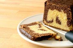 O chocolate marmoreou o plumcake, cortando com uma faca cerâmica Imagem de Stock