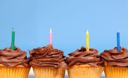 O chocolate quatro geou queques em uma fileira com as velas Fotografia de Stock Royalty Free