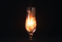 O chuveirinho em um fundo preto, faíscas voa em sentidos diferentes, vidro elegante, Imagem de Stock