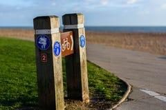 O ciclismo e o pedestre assinam apontar à estrada da frente marítima Fotografia de Stock Royalty Free
