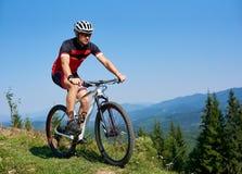 O ciclista atlético feliz do turista no capacete, os óculos de sol e a equitação completa do equipamento bike no monte gramíneo imagens de stock