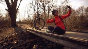 O ciclista caucasiano feliz da mulher faz a uma foto dsi mesma um selfie no telefone ao sentar-se na ponte sobre um rio dentro fotos de stock