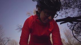O ciclista caucasiano novo do turista do atleta da mulher usa uma ferramenta, uma bomba de bicicleta para inflar o ar em uma mont vídeos de arquivo