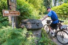 O ciclista, com Mountain bike em um trajeto da sujeira, observa um sinal direcional imagem de stock