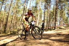 O ciclista compete na raça da elite MTB na floresta Fotos de Stock