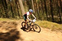 O ciclista compete na raça da elite MTB na floresta Fotografia de Stock Royalty Free