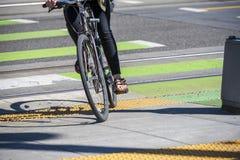 O ciclista cruza a estrada com os trilhos do bonde em cruzamento especialmente marcado fotografia de stock royalty free