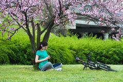 O ciclista da menina está descansando sob uma árvore imagem de stock royalty free
