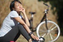 O ciclista de relaxamento da mulher aprecia o sol imagens de stock royalty free