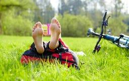 O ciclista descalço em uma parada lê o encontro na grama verde fresca Imagem de Stock