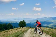 O ciclista do desportista no corta-mato do sportswear e da equitação do capacete bicycle na estrada da montanha fotos de stock