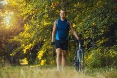 O ciclista do homem monta trajetos de floresta Imagem de Stock