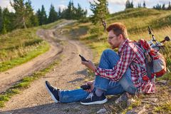 O ciclista do homem novo senta-se na borda de uma estrada de terra fotos de stock