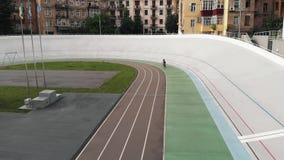 O ciclista fêmea atrativo novo da estrada está montando no velodrome Menina na trilha de ciclismo Conceito do ciclismo opini?o do vídeos de arquivo
