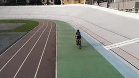 O ciclista fêmea na bicicleta da estrada está treinando no velodrome Feche acima da menina desportivo na bicicleta na trilha de c video estoque