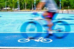 O ciclista masculino monta uma bicicleta na pista do sinal da bicicleta fotografia de stock